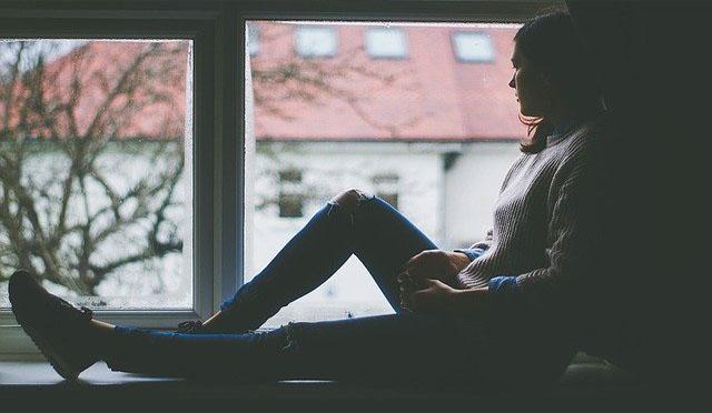 mujer en sombra sentada ventana