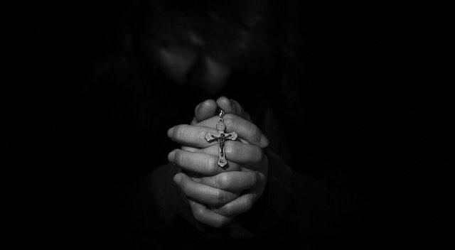 rezando cruz entre las manos