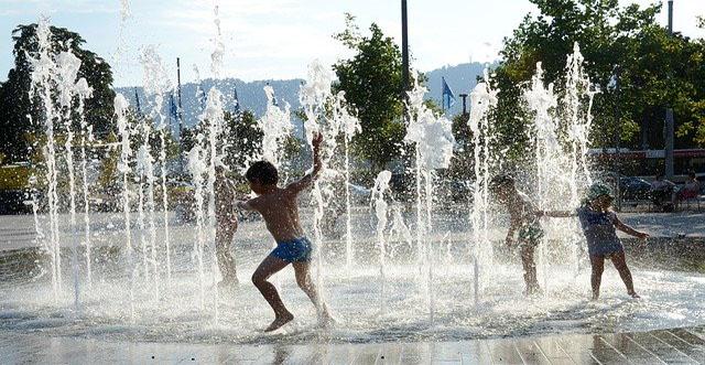 niños jugando fuente agua